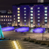 Illuminated fountains in Granary Square, King's Cross, by the Fountain Workshop next to a Christmas tree art installation