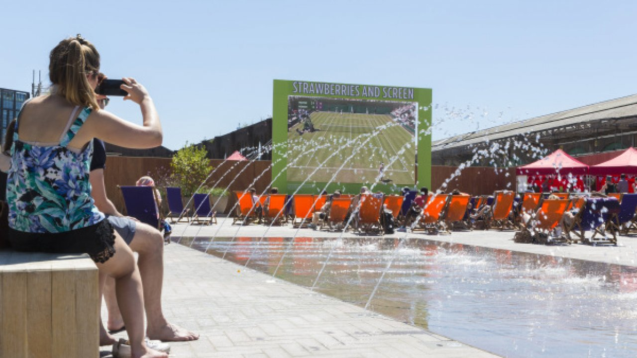 People watching Wimbledon in Cubitt Square, King's Cross, next to fountains by the Fountain Workshop